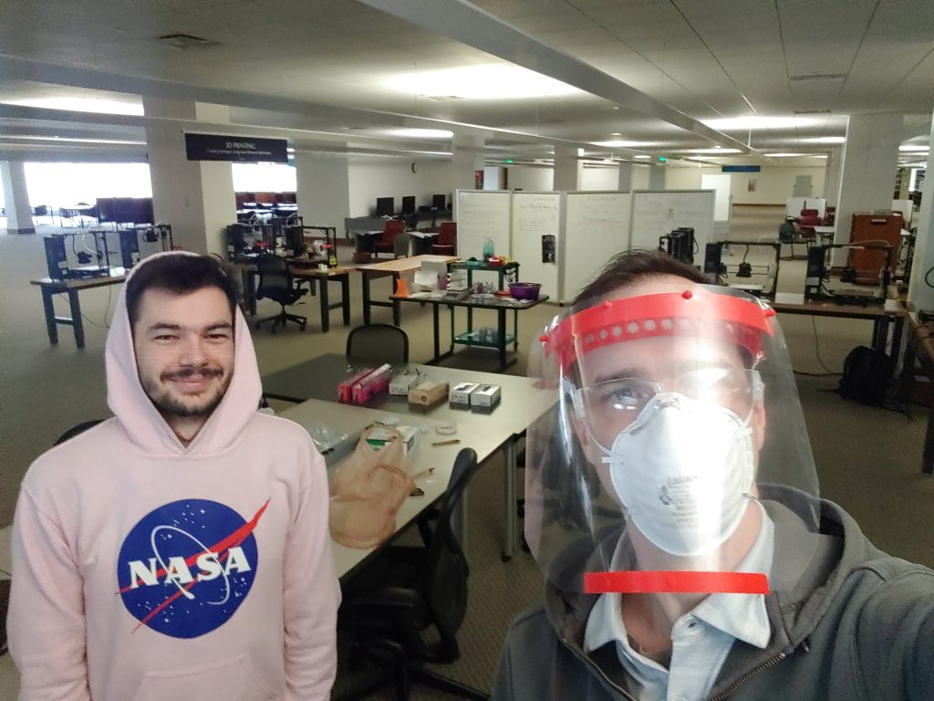 Two library staff, one smiling and the other with a face shield and mask