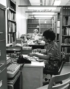 Librarians work at desks in the B-Level Medical Sciences Library at the University of Utah in the 1960's.