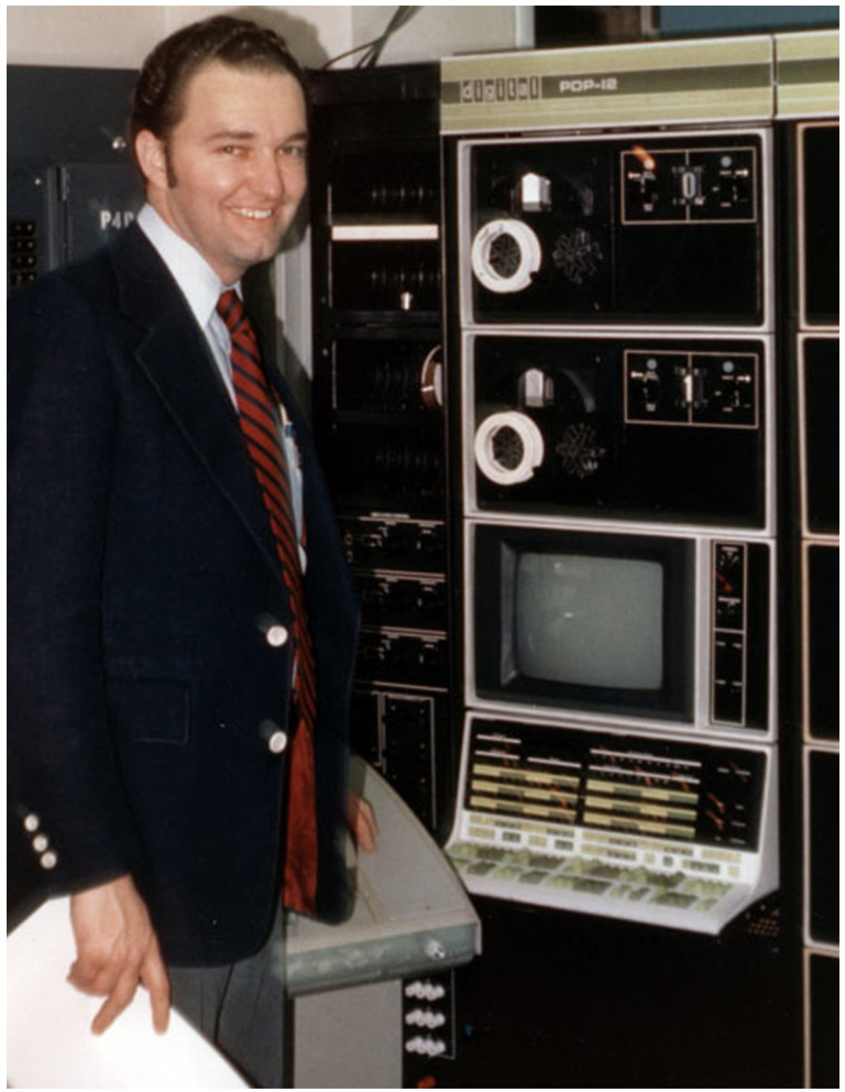 Dr. Reed Gardner standing in front of old computer